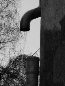 Fallrohr mit Winkel und Zwischenraum trifft nicht das untere Rohr. Wasser fließt daneben. Schwarz/weiß