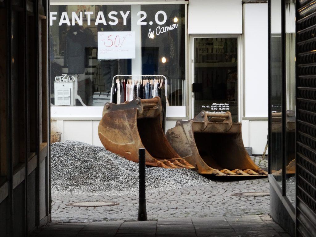 """zwei leere Baggerschaufeln, im Hintergrund die Schaufensterbeschriftung """"Fantasy 2.0"""""""