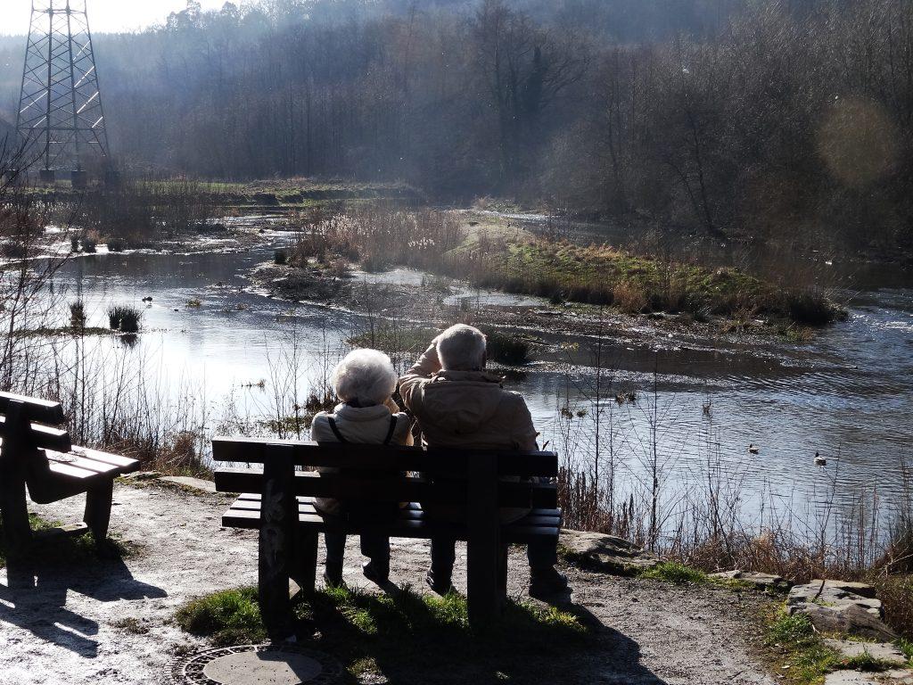 Ein Rentnerpaar sitzt in der Sonne auf einer Bank, vor ihnen der neue Verlauf der Hönne