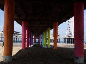 unter der Seebrücke Schreveningen, farbige Betonsäulen, rechts das Riesenrad, links das Restaurant