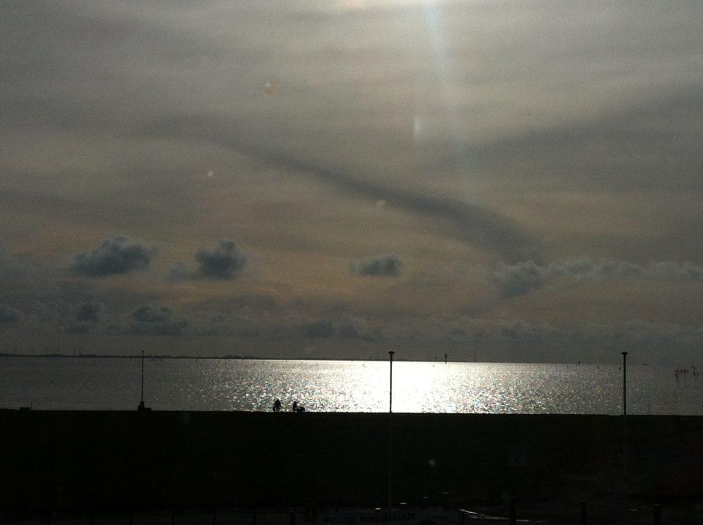 Blick auf einen verhangenen Himmel. irgendwo oben Sonne, dann ein Sreifen glänzendes Meer, eine Familie mit .Kinderwagen und drei Straßenlampen.