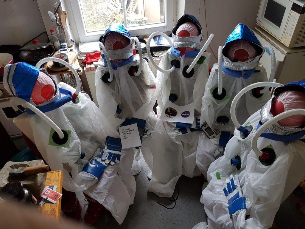 Fünf Astronautinnen, die im Anzug in der Küche sitzen und der Dinge harren, die da kommen sollen.