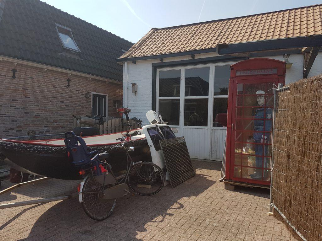 Ein Boot, ein Fahrrad, eine rote Telefonzelle, innen ein Papppolizist, alles vor einer Garage.