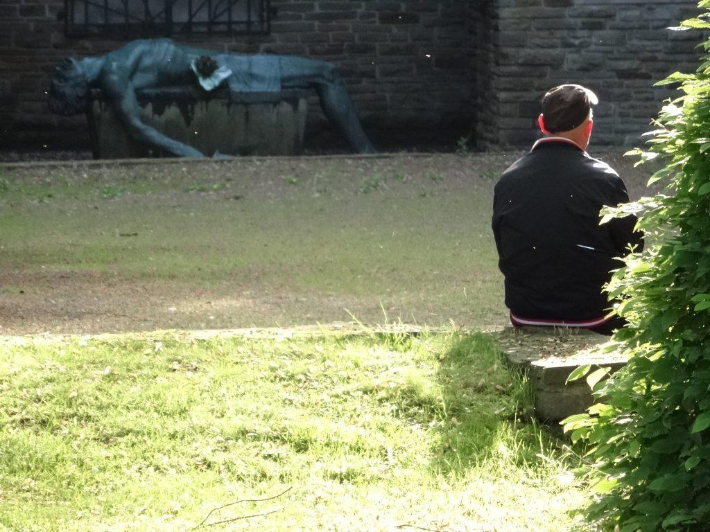 Alter Mann mit Schirmmütze, auf einer Mauer sitzend, im Hintergrund ein Kriegerdenkmal des ersten und zweiten Weltkrieges. Der gefallene Krieger - Bronze