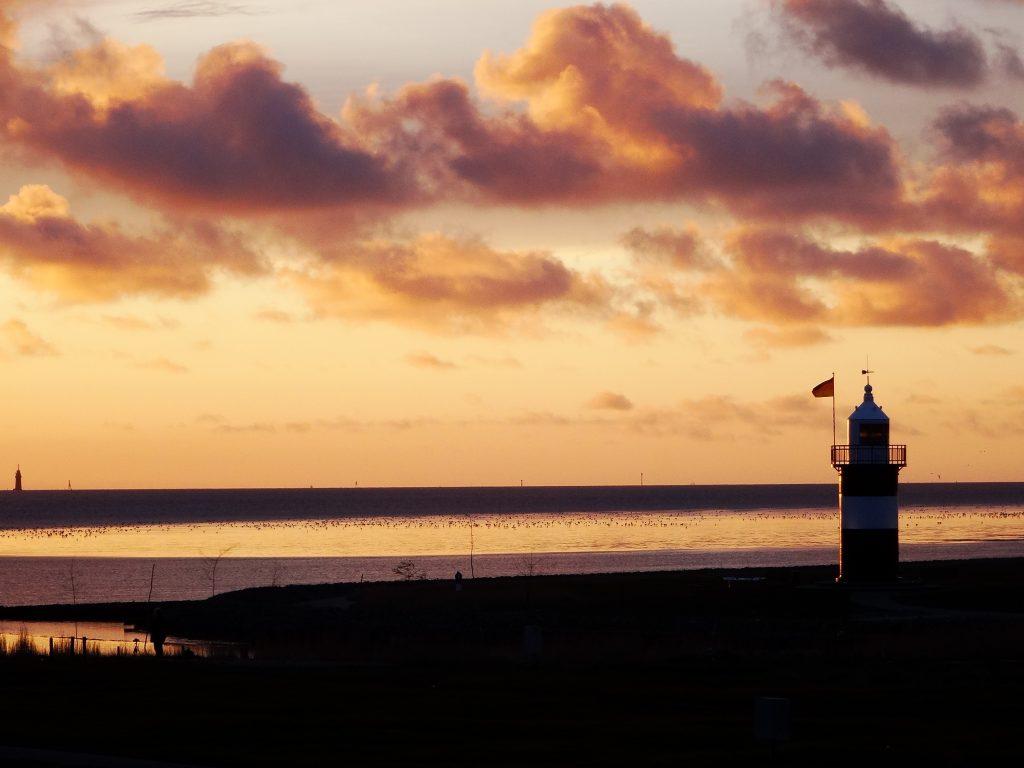 Sonnenuntergang Nordsee mit einem Leuchtturm im Vordergrund und einem im Hintergrund, dazwischen Wasser und Watt.