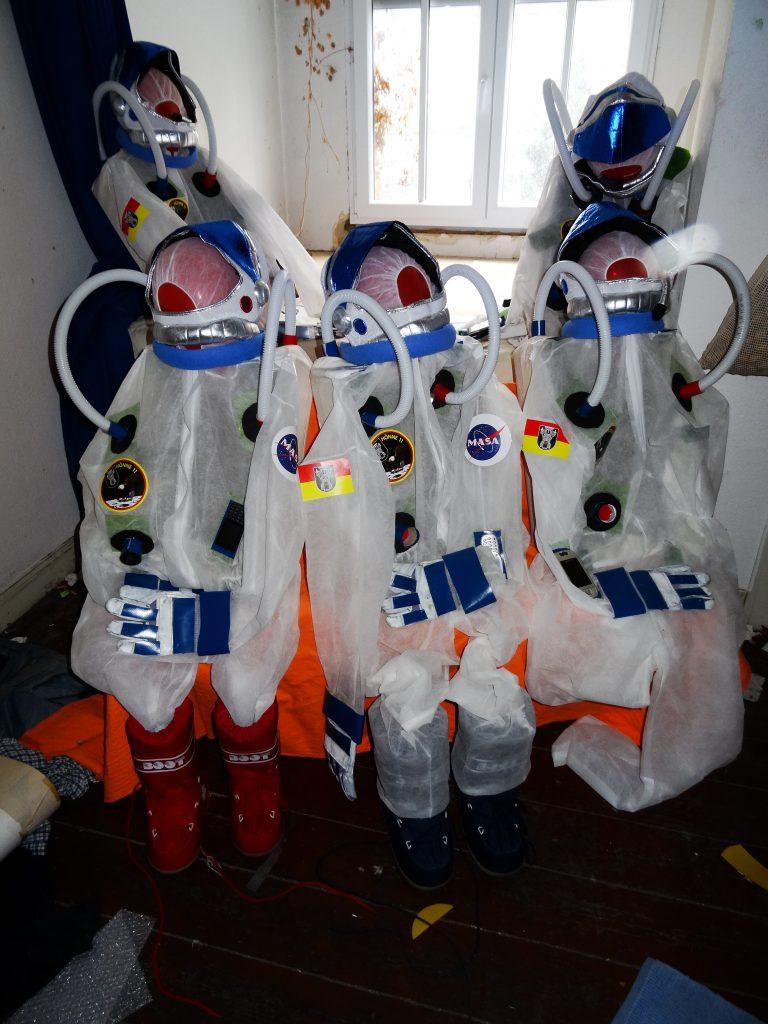 Fünf AstronautInnenanzüge warten auf den Einsatz